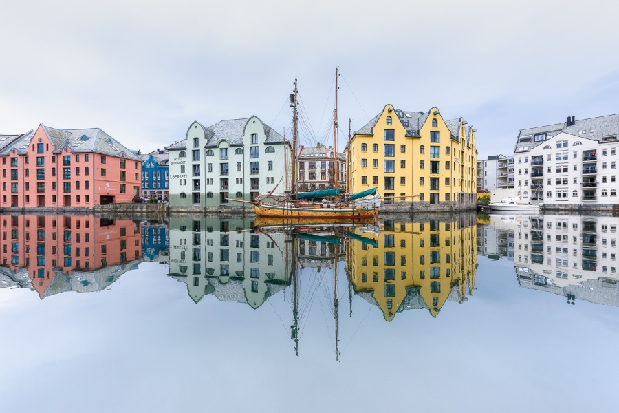 A reflection on the sea of a ship and four colored houses on the back